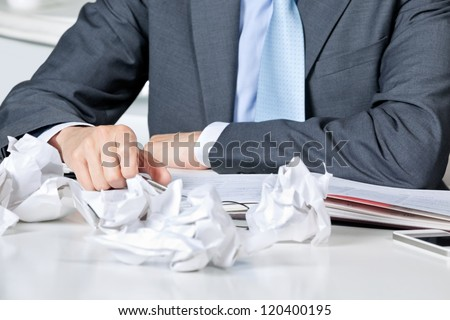 Midsection of businessman sitting at desk with crumpled papers