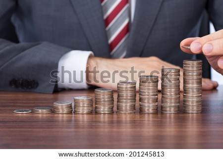 Midsection of businessman stacking coins in increasing order at desk