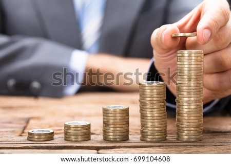 Shutterstock Midsection of businessman stacking coins in increasing order on wooden table