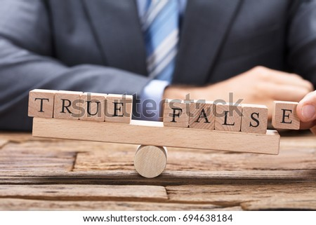 Midsection of businessman with true and false wooden blocks on seesaw at table