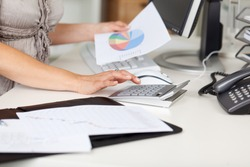 Midsection of businesswoman holding piechart while using calculator at office desk