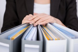 Midsection of businesswoman with binders at office