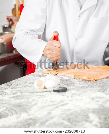 Midsection of chef cutting ravioli pasta at messy commercial kitchen counter