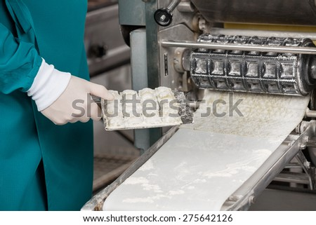 Midsection of chef holding ravioli pasta tray by machinery at commercial kitchen