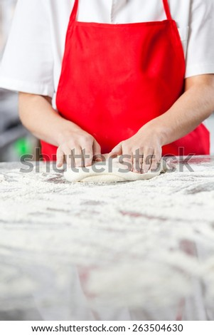 Midsection of chef kneading dough at messy counter in commercial kitchen