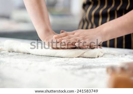 Midsection of chef pressing dough at messy counter in commercial kitchen