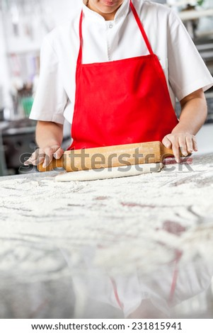 Midsection of chef rolling dough at messy counter in commercial kitchen