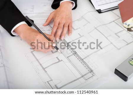 Midsection of female architect with model house, blueprints and spirit level on office desk
