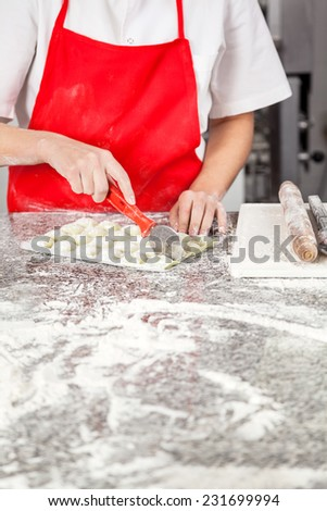 Midsection of female chef cutting ravioli pasta at messy counter in commercial kitchen