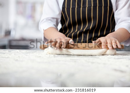 Midsection of female chef rolling dough at messy counter in commercial kitchen