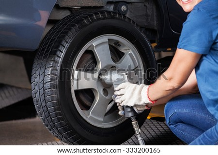 Midsection of female mechanic using pneumatic wrench to fix car tire at repair shop