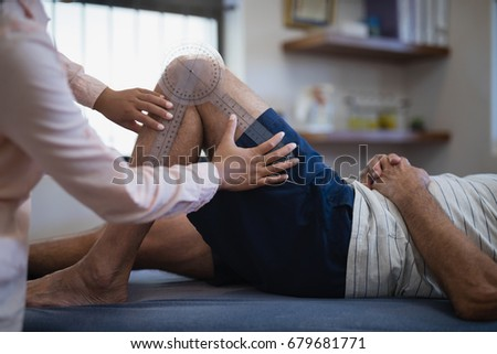 Midsection of female therapist measuring knee while senior male patient lying on bed at hospital ward