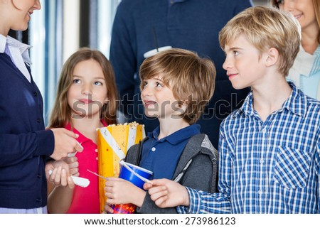 Midsection of female worker checking movie tickets of family at cinema