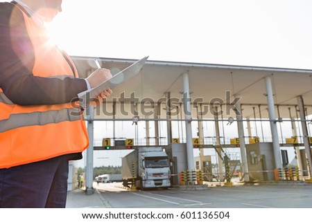 Midsection of female worker writing on clipboard while looking at truck entering in shipping yard #601136504