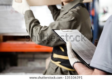 Midsection of foreman loading cardboard box with supervisor holding clipboard at warehouse