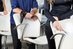 Midsection of hairdressers with dryer and scissors standing behind chairs in salon