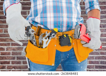 Midsection of handyman holding hand tools against red brick wall