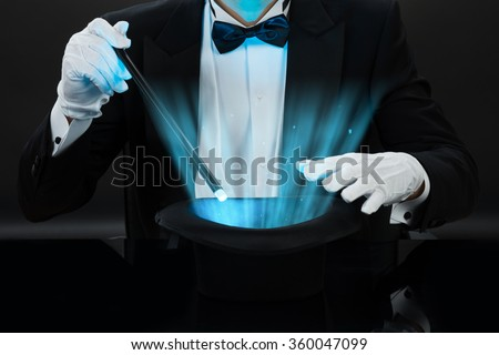 Midsection of magician holding magic wand over illuminated hat against black background #360047099