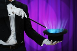 Midsection of magician holding magic wand over illuminated hat against purple curtain