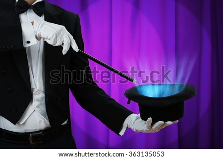 Midsection of magician holding magic wand over illuminated hat against purple curtain #363135053