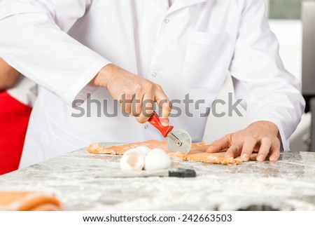 Midsection of male chef cutting ravioli pasta at messy counter in commercial kitchen