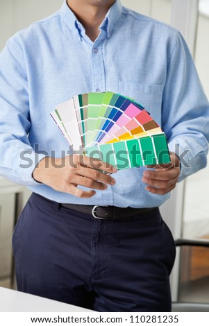 Midsection of male interior designer holding fanned out color swatches - stock photo