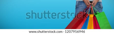 Midsection of man carrying colorful shopping bag against white background against plain blue background #1207956946