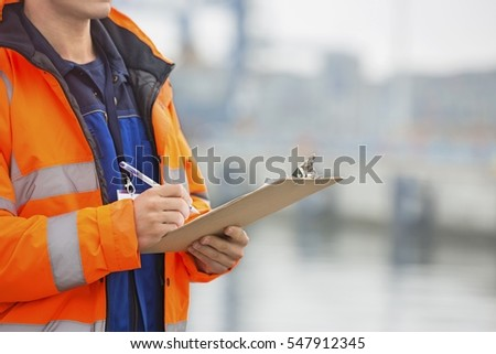 Midsection of mid adult man writing on clipboard in shipping yard