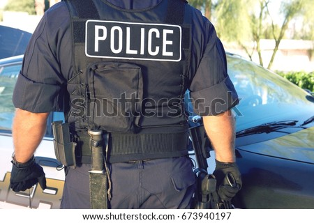 Midsection of policeman in uniform standing against car Stock fotó ©