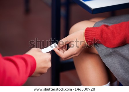 Midsection of schoolchildren passing cheat sheet during examination in classroom