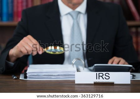Midsection of tax auditor examining documents with magnifying glass at table in office