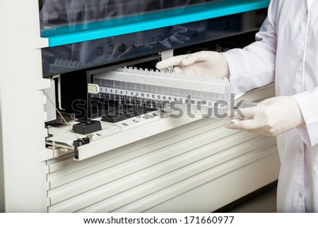 Midsection of technician placing samples in analyzer at laboratory