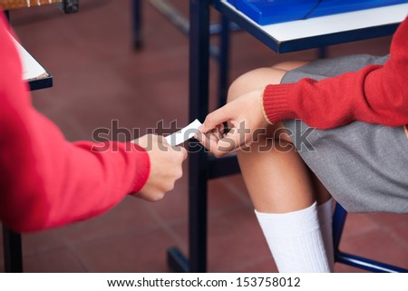 Midsection of teenage girl and boy passing cheat sheet at desk in classroom