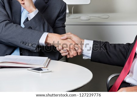 Midsection of two businessmen shaking hands at desk in office