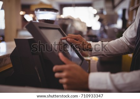 Midsection of waiter touching computer monitor at counter in coffee shop