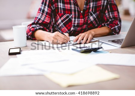 Midsection of woman writing in notepad while sitting at table. Working from home in quarantine lockdown. Social distancing Self Isolation