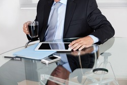 Midsection of young businessman with coffee cup using digital tablet at desk in office