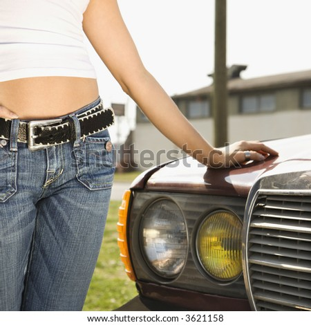Midsection of young Caucasian woman standing beside automobile. - stock photo