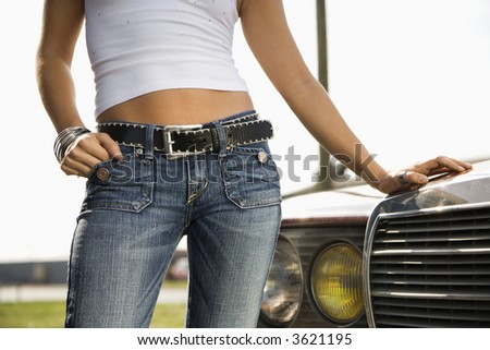Midsection of young Caucasian woman standing beside automobile.