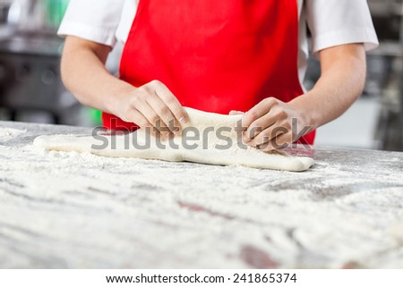 Midsection of young female chef kneading dough at messy counter in commercial kitchen