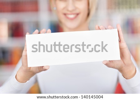 Midsection of young woman holding blank sign in library #140145004