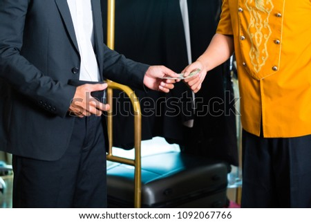 Midsection view of man giving tip to employee in hotel