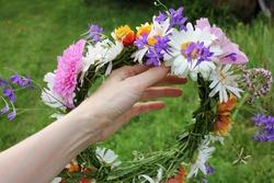Midsummer flower wreath in woman hand on green grass background. Scandinavian summer celebration. Greenery wedding idea. DIY floral crown. Midsummer night dream decoration. Farm rustic lifestyle.