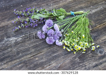 midsummer medical herbs bunch on old wooden background. sage, chamomile and onion blossoms