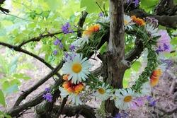 Midsummer Wreath of wildflowers hanging on a wooden pole on green leaves background in the garden. Scandinavian summer celebration. Greenery wedding idea. Midsummer night dream decoration. Farm rustic
