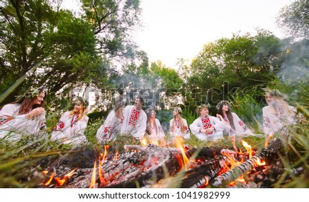 Midsummer. Young people in Slavic clothes sitting in the woods near the fire. #1041982999