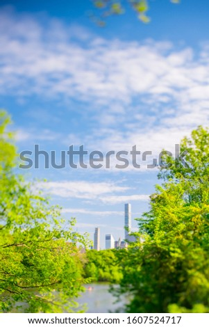 Midtown Manhattan skyscraper stand beyond the many growing fresh green trees along The Lake in Central Park in Central Park New York City NY USA on May. 08 2019.