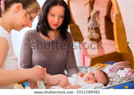 Midwife examining newborn baby at postnatal care in practice Stock photo ©