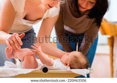 Midwife examining newborn baby at postnatal care in practice checking weight with scale Stock photo ©