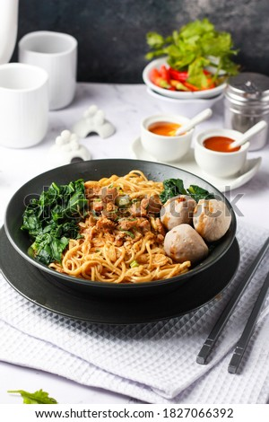 Mie ayam is a common Indonesian dish of seasoned yellow wheat noodles topped with diced chicken meat (ayam), beef meatballs (bakso), served on black ceramic bowl. Selective focus, blurry Zdjęcia stock ©